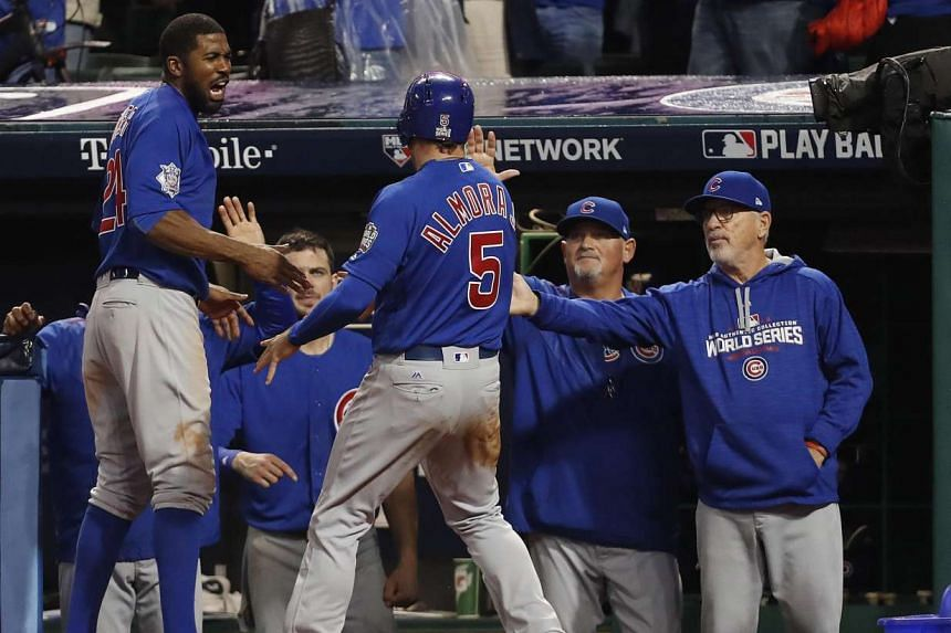 Chicago Cubs baserunner Albert Almora Jr. (centre) celebrates after he scores on batter Ben Zobrist's RBI double in the top of the tenth inning.