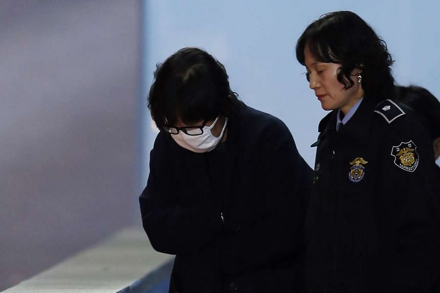 Choi Soon Sil (left) being escorted after her formal arrest, at the Central District Court in Seoul, on Nov 3, 2016.