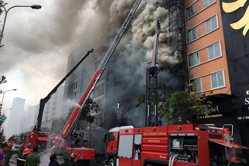 Firefighters battling the blaze that broke out at a karaoke bar in Hanoi on Tuesday. The fire killed 13 people and took five hours to put out. Some victims likely suffocated in windowless rooms, officials have said.