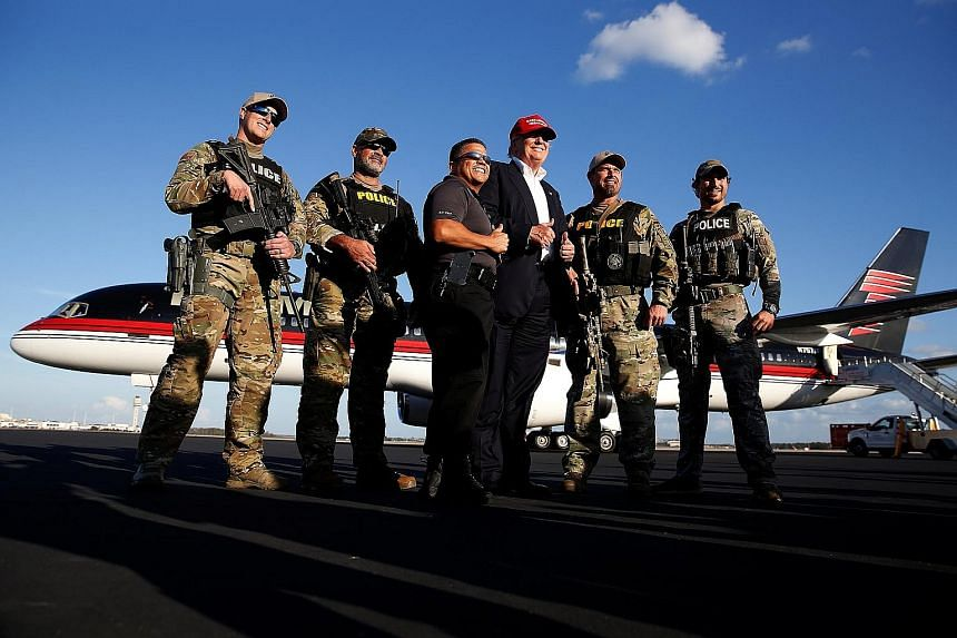 Mr Trump having a picture taken with law enforcement officers after a campaign event in Orlando on Wednesday. His populist campaign has energised militia members who admire his promises to deport illegal immigrants, stop Muslims from entering the cou