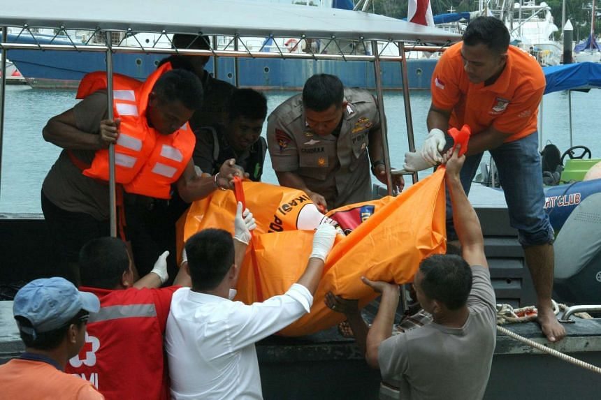 Officers evacuate the dead body of an Indonesian migrant worker as a speedboat from Malaysia sank off Batam Island, in Teluk Mata Ikan, Batam on Nov 2, 2016.