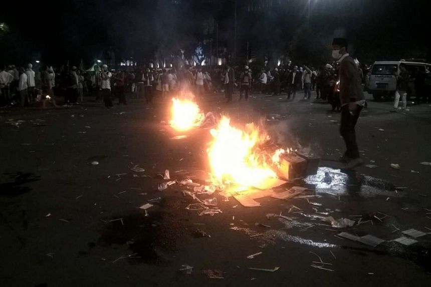 Protesters burn garbage near presidential palace in Jakarta during a rally calling for Governor Basuki Tjahaja Purnama to step down.