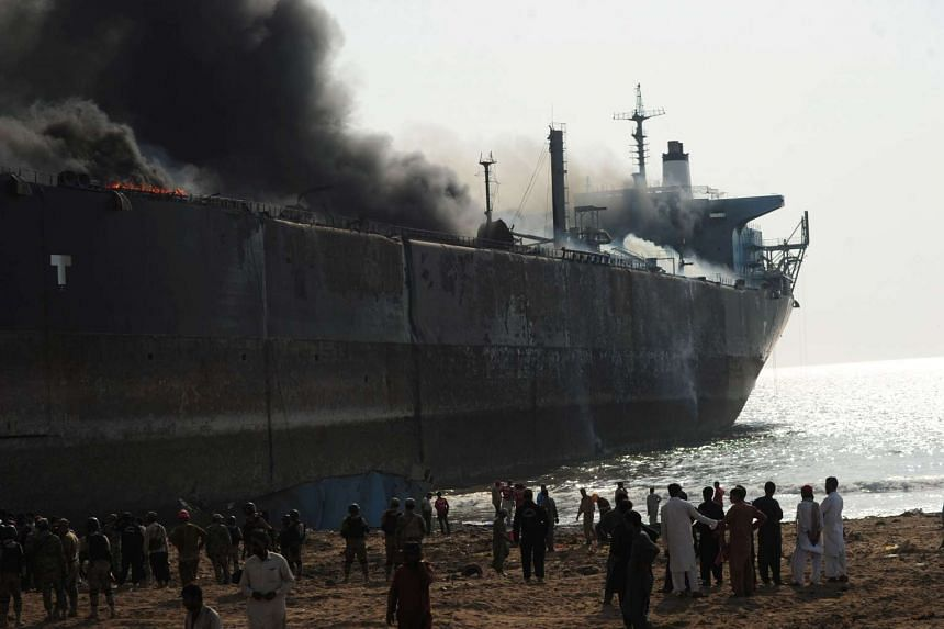 Pakistani workers gathering around the burning wreckage of a ship, after a gas cylinder exploded in the Gadani shipbreaking yard on Nov 1, 2016.