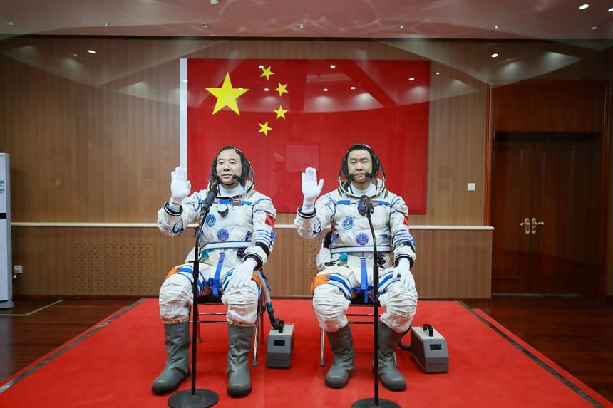 Chinese astronauts Jing Haipeng (left) and Chen Dong wave in front of a Chinese national flag before the launch of Shenzhou-11 manned spacecraft in Jiuquan, China on Oct 17, 2016.