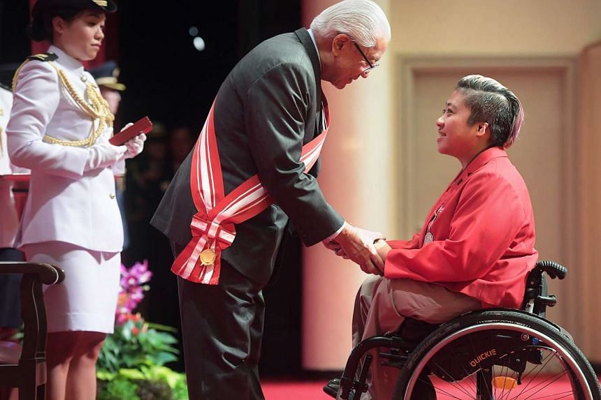 Para-swimmer Theresa Goh receives the Public Service Star from President Tony Tan at the 2016 National Day Awards on Sunday (Nov 6) at the University Cultural Centre.