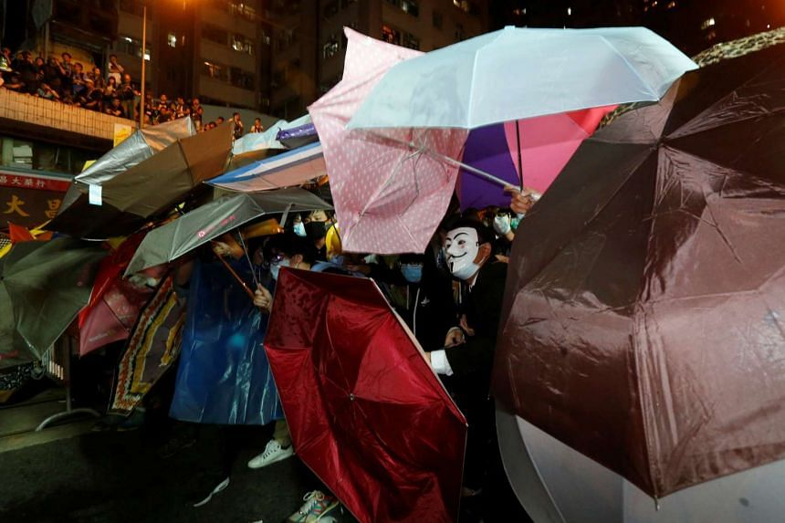 Demonstrators using umbrellas to try to protect themselves from pepper spray during clashes with police in Hong Kong, on Nov 6, 2016.