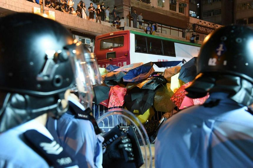 Protesters using umbrellas to try to protect themselves from pepper spray during a stand-off with police officers during a protest in Hong Kong, on Nov 6, 2016.