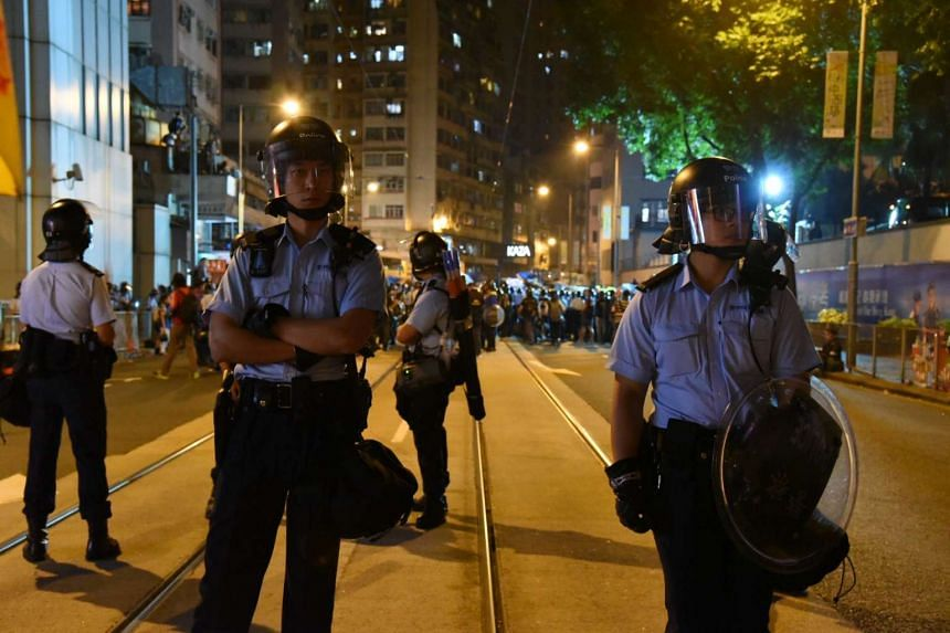 Police officers in riot gear standing guard on a street in Hong Kong, during protests against what is seen as Chinese interference in a controversy involving Hong Kong lawmakers, on Nov 6, 2016.