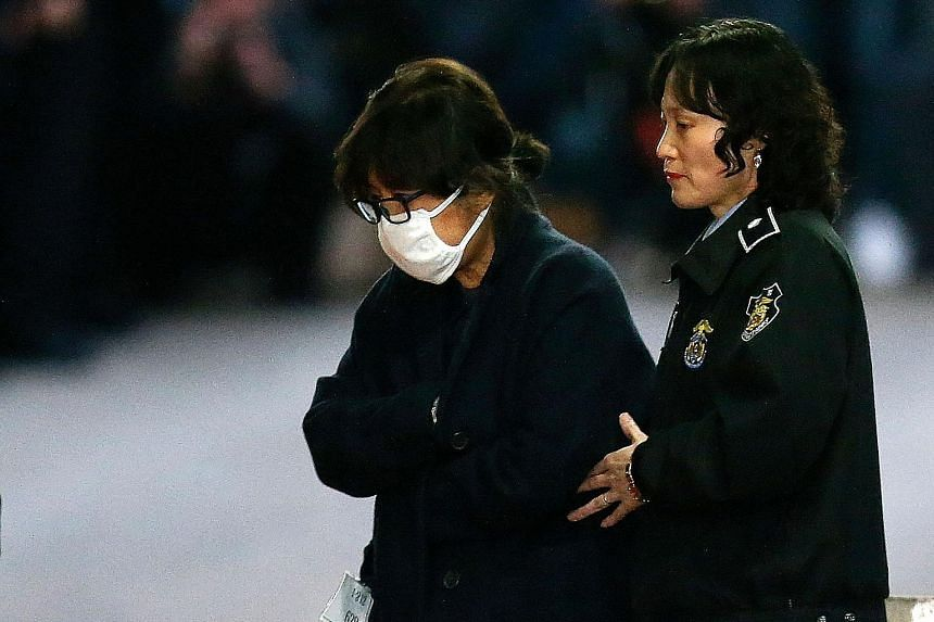 Ms Choi being escorted from the Central District Court in Seoul after her formal arrest last Thursday. She had returned to South Korea from Germany last Monday to submit herself to investigations.