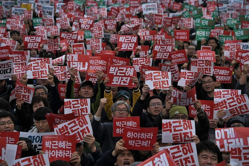 South Korean protesters with placards demanding the resignation of President Park Geun Hye in Seoul yesterday. Police estimated more than 40,000 protesters took to the streets to rally against Ms Park, who is ensnared in an influence-peddling scandal