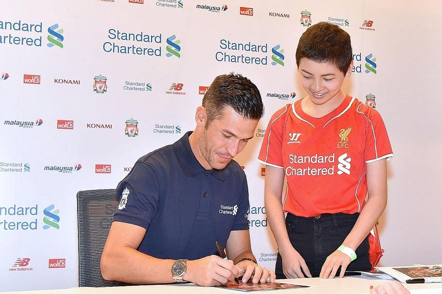 Former Liverpool player Luis Garcia signing an autograph for Reds fan Lauren Ong. The Make-A-Wish Foundation will be paying for Lauren and her family to watch a home game at Anfield.