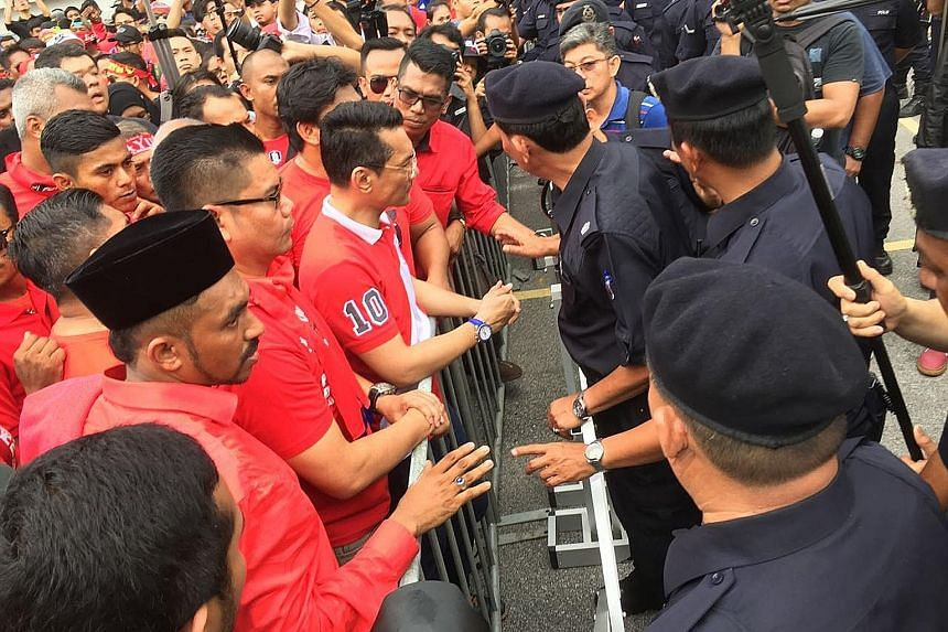Red Shirt supporters being stopped by police near the office of Malaysiakini in Petaling Jaya yesterday. The protesters have accused the news portal of receiving foreign funds to topple Prime Minister Najib Razak's government.