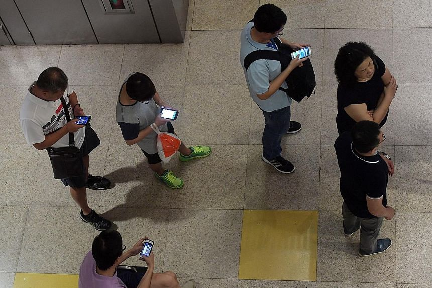 Commuters accessing mobile services on the Circle Line in Bishan station yesterday. Tests were done during the shutdown to isolate the cause of the signalling faults that have affected the line since Wednesday.