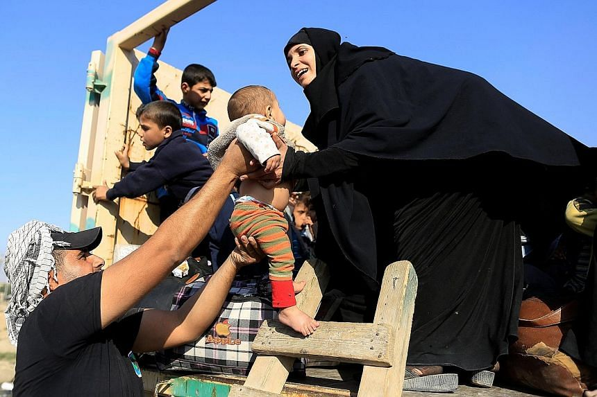 A soldier handing a baby to its mother, who had just fled the Samah district of eastern Mosul, on board a military truck at the Iraqi Special Forces checkpoint in Kokjali, east of Mosul, yesterday.