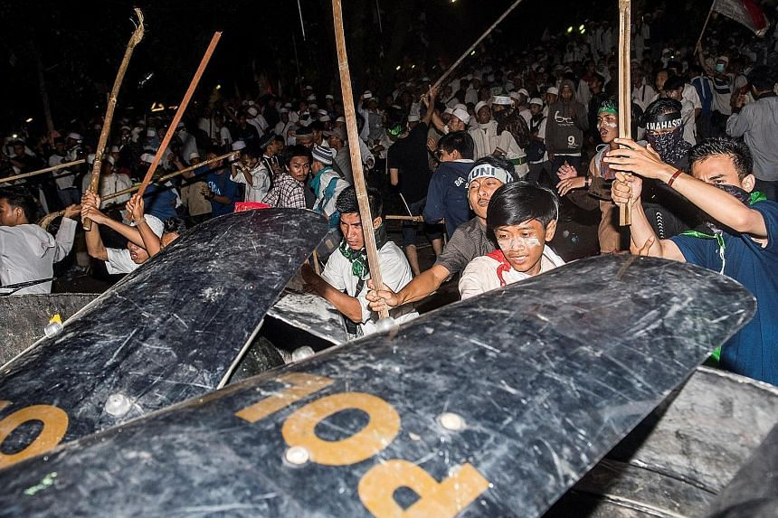 Muslim hard-line protesters clashing with anti-riot policemen during last Friday's protest against Jakarta Governor Basuki Tjahaja Purnama, a Chinese Christian, who is accused of insulting Islam.