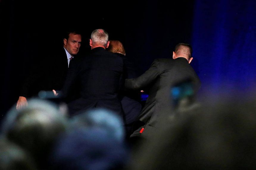 Presidential nominee Donald Trump is hustled off the stage by security agents at a campaign rally in Reno, Nevada.