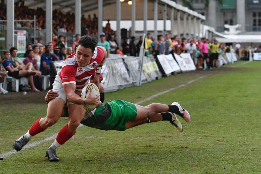England Academy's Callum Sirker (in red) attempting to score a try against Sunnybank's Junior Laloifi during the SCC 7s finals at the Padang on Nov 6, 2016.