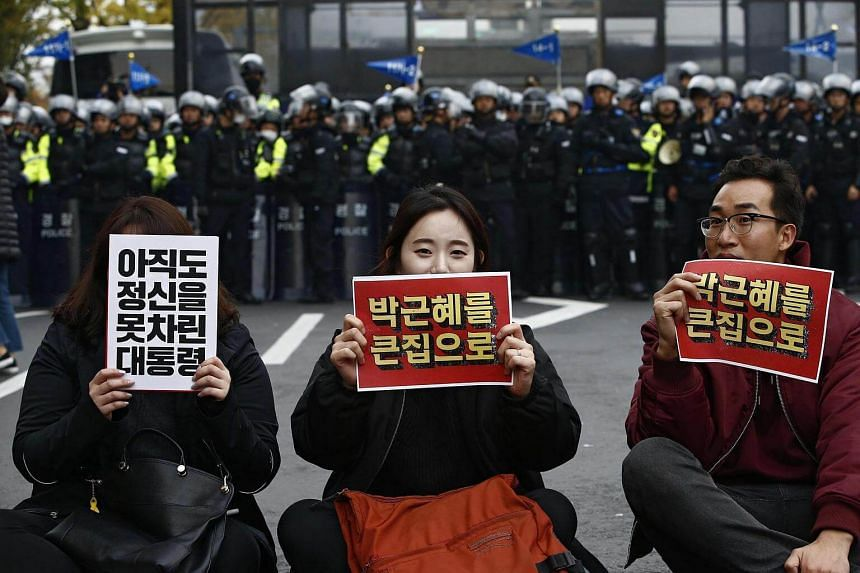 """South Koreans hold up banners that read """"Park Geun Hye out"""" during a protest against the President in Seoul."""