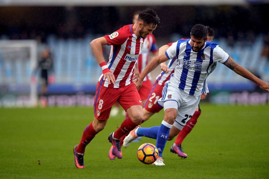 Atletico Madrid's Saul (left) fights for the ball with Real Sociedad's Raul Navas.