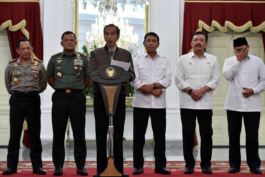 Indonesian President Joko Widodo (third from left) talks to reporters at the Presidential Palace in Jakarta on Nov 5, 2016.