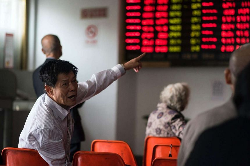 An investor gestures in front of the stock price movements on a screen at a securities company in Shanghai on Nov 7, 2016.