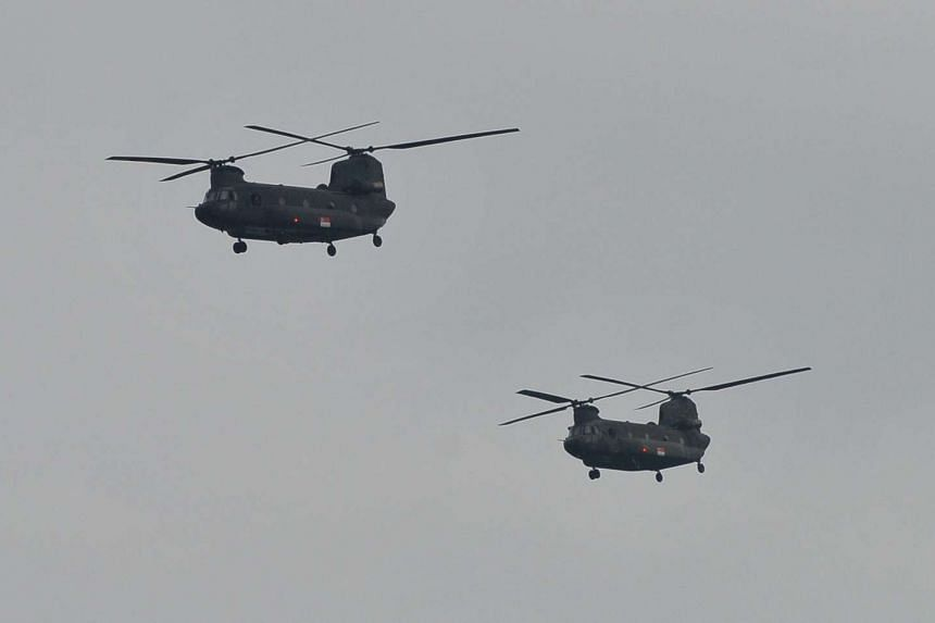Two RSAF Chinook helicopters flying over Marina South Pier.