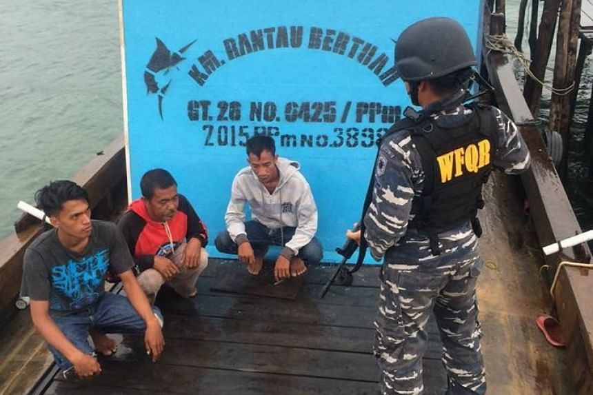 A navy soldier guarding suspects after boarding a fishing boat for allegedly taking Singaporeans fishing without a permit, in waters near Bintan, on Nov 4, 2016.