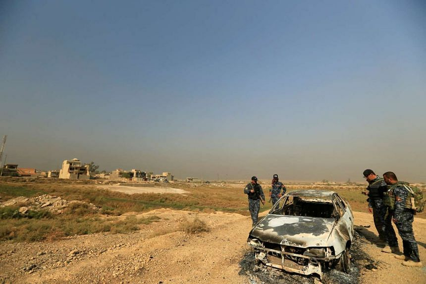 Iraqi security forces inspect a destroyed vehicle from clashes in Hammam al-Ali, south of Mosul, Iraq on Nov 7, 2016.