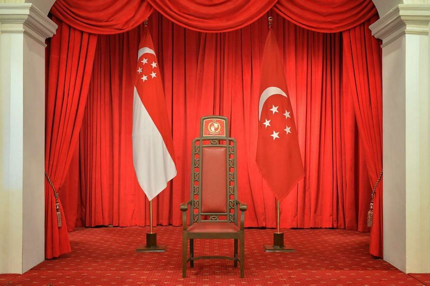 The president's chair, flanked by the state flag and the presidential flag at the Istana.