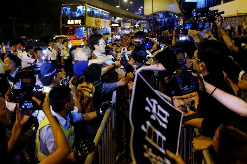 Demonstrators clash with police during a protest against what they call Beijing's interference over local politics and the rule of law, a day before China's parliament is expected to announce their interpretation of the Basic Law in light of two pro-