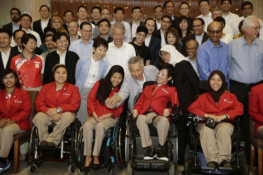 Prime Minister Lee Hsien Loong takes a selfie with Paralympians Yip Pin Xiu and Toh Sze Ning before the official photoshoot at Parliament House on Nov 7, 2016.