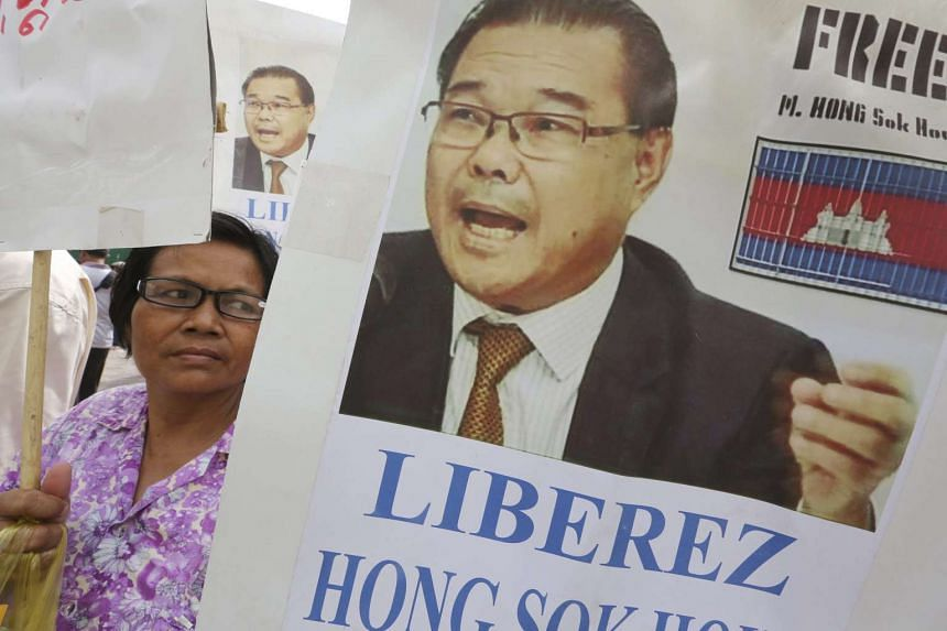 A Cambodian supporter holds placards with portraits of opposition Senator Hong Sok Hour outside the Municipal Phnom Penh Court on Oct 26, 2016.