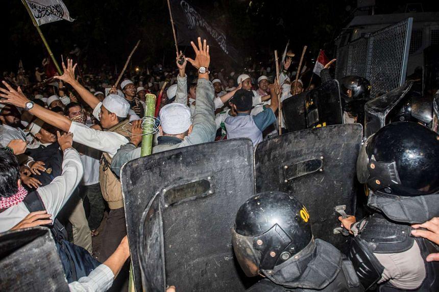 Muslim hardline protesters clash with anti-riot policemen during a protest against Jakarta's incumbent governor Basuki Tjahaja Purnama on Nov 4, 2016.