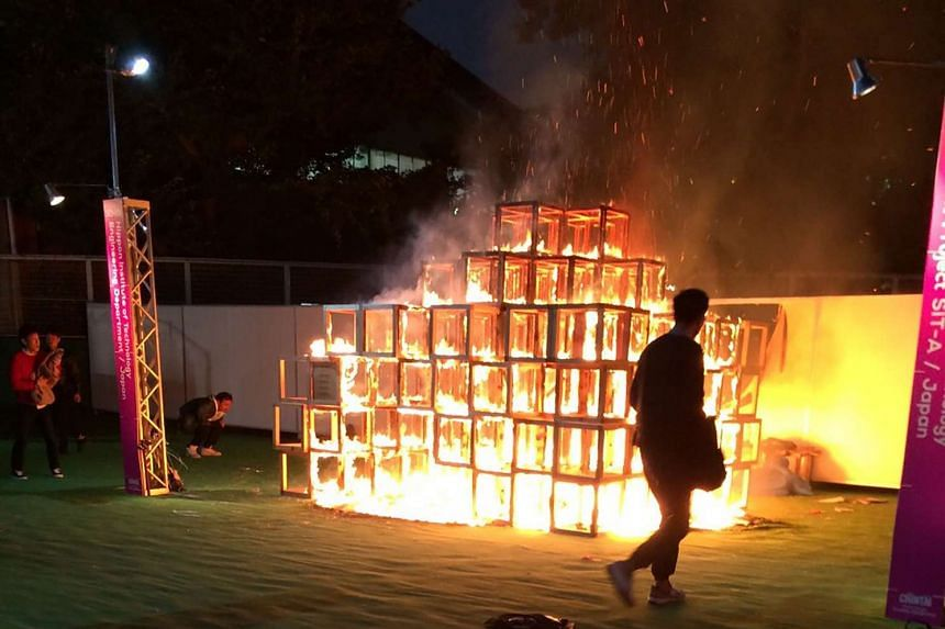People look at a burning wooden jungle gym displayed at a Tokyo art festival on Nov 6, 2016.