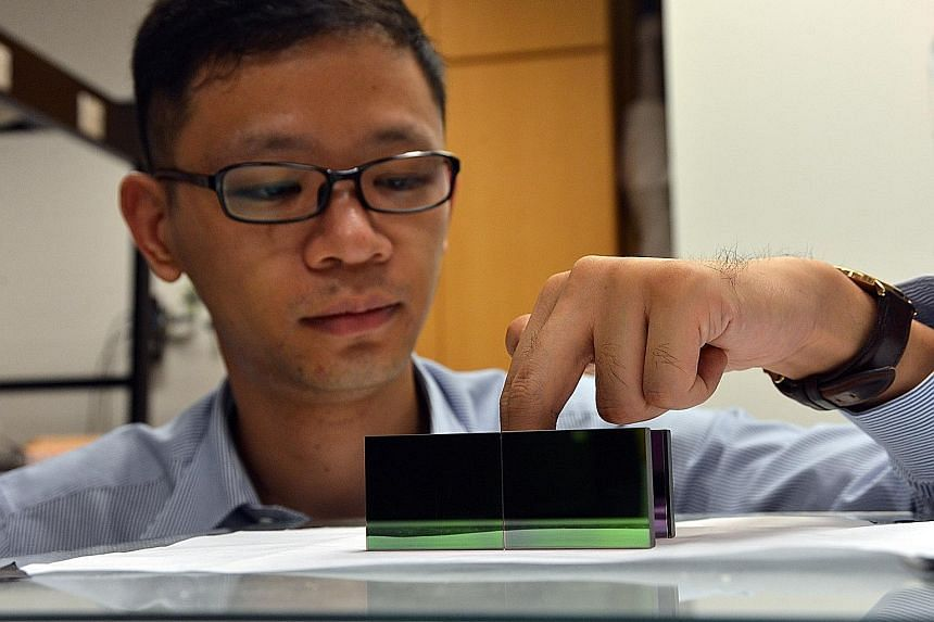 """NTU scientist Zhang Baile putting his fingers into the new """"invisibility cloak"""", showing how it can hide heat signatures, making objects undetectable, even with thermal imaging (left)."""