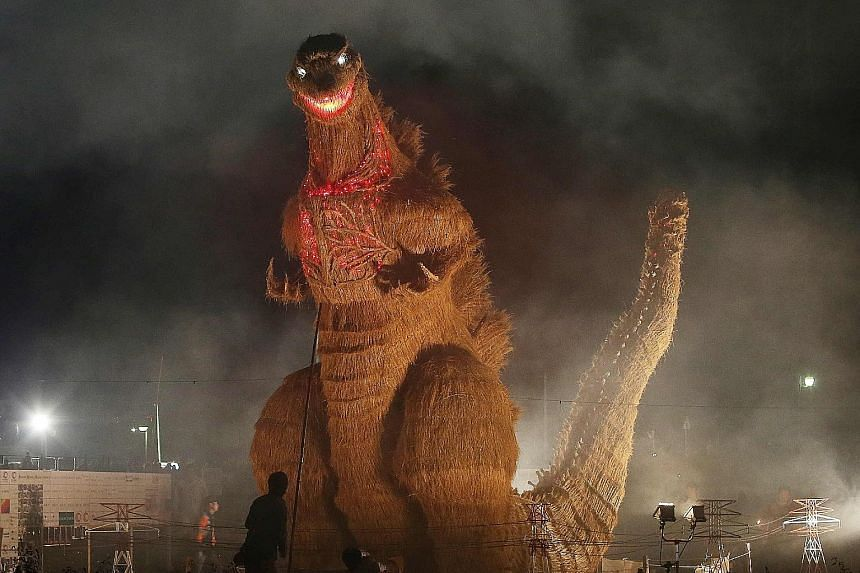 A 7m-tall Godzilla figure - made from wood and bamboo and covered with straw - on display at the autumn festival in Chikuzen in Japan's Fukuoka prefecture on Saturday. It was created by about 210 volunteers.