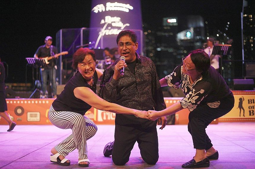 """Left: Madam Anna Sharp, 61, playing the """"air guitar"""" while dancing to Blame It On The Boogie at the Esplanade Outdoor Theatre, performed as part of the four-day A Date With Friends festival. Far left: Veteran singer Joe Chandran singing Danny Boy as"""