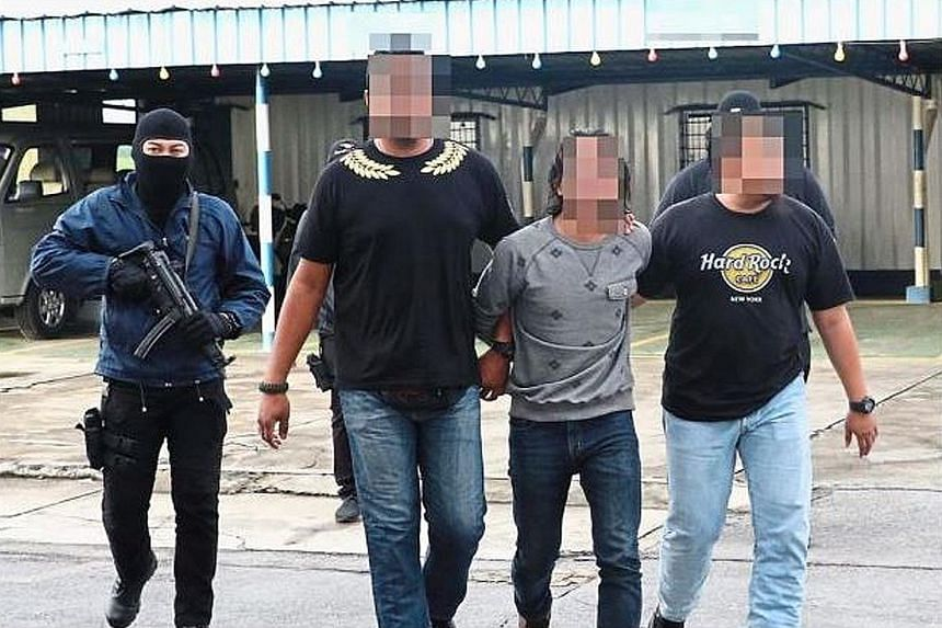 One of the Black Crow members (in light-coloured T-shirt) being escorted by police. A 29-year-old technician and a 24-year-old labourer were given about RM5,000 by Malaysia's most-wanted militant, Mohamad Wanndy Mohamad Jedi, to travel to Syria.