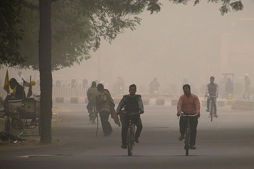Young runners took part in the New Delhi 10K Challenge amid the severe air pollution, while adults were spotted playing cricket or cycling in heavy smog (above).