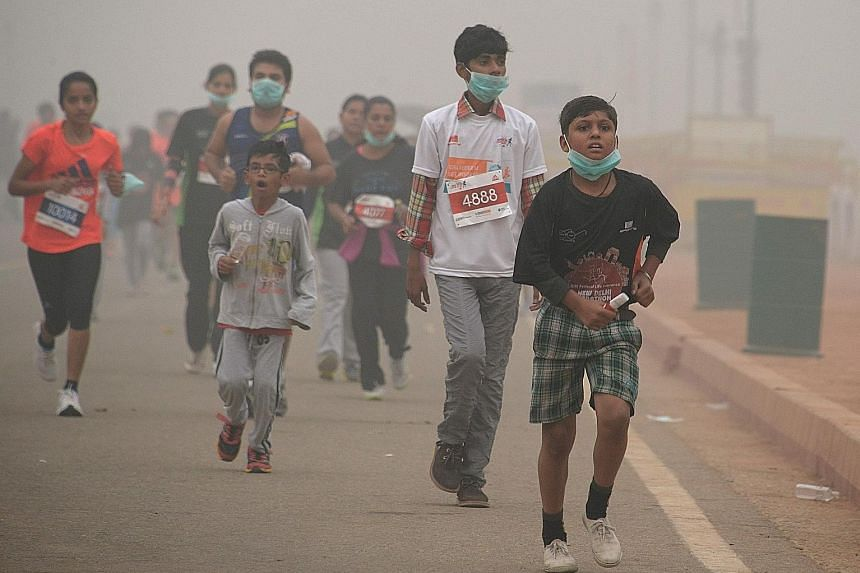 Young runners took part in the New Delhi 10K Challenge amid the severe air pollution (above), while adults were spotted playing cricket or cycling in heavy smog.