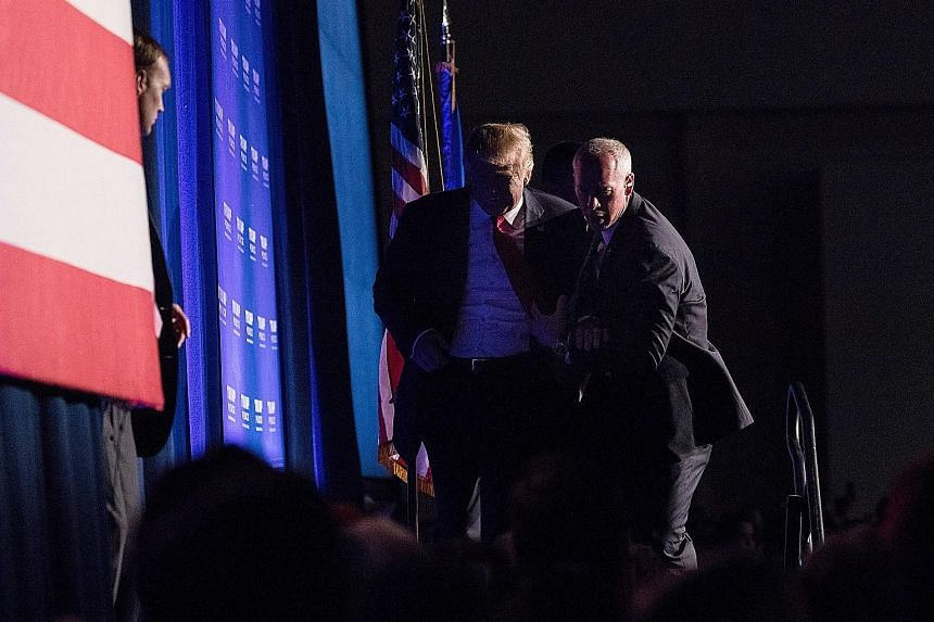 "Mr Trump being rushed off the stage by Secret Service agents after someone in the crowd yelled ""gun"" at his rally in Reno, Nevada, on Saturday. No weapon was found on the man thought to be a threat to him, and the Republican candidate returned minute"