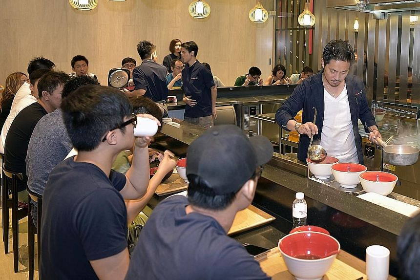 Tsuta's chef-owner Yuki Onishi cooking at the outlet at Pacific Plaza.