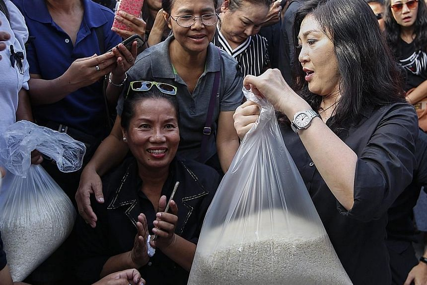 Former premier Yingluck Shinawatra (far right) selling sacks of rice that she bought from struggling farmers in north-east Thailand to delighted shoppers in Bangkok on Saturday.