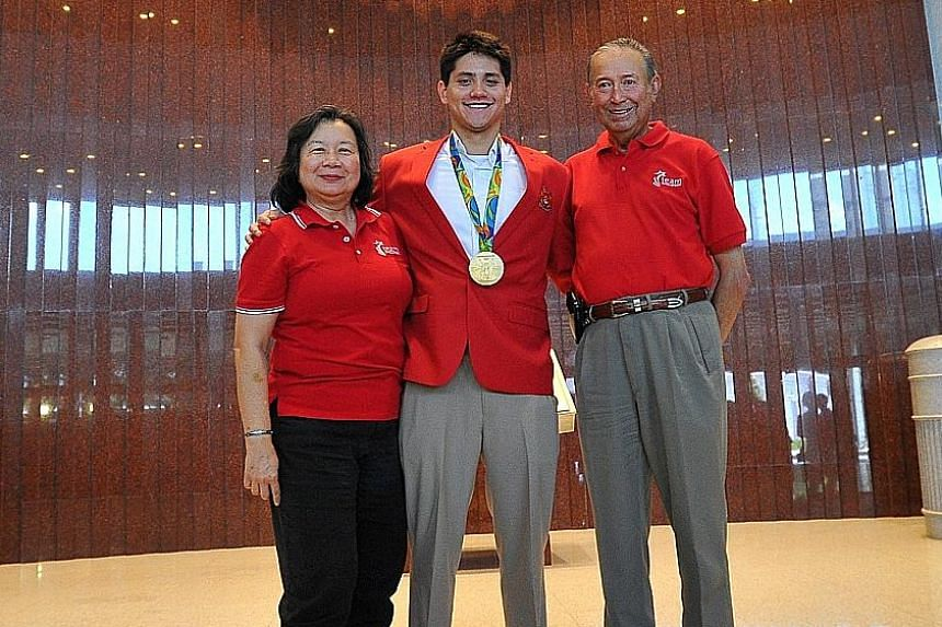 Joseph Schooling with his proud parents May and Colin at Parliament House in August. The swimmer is the first athlete in Singapore to be honoured in Parliament.