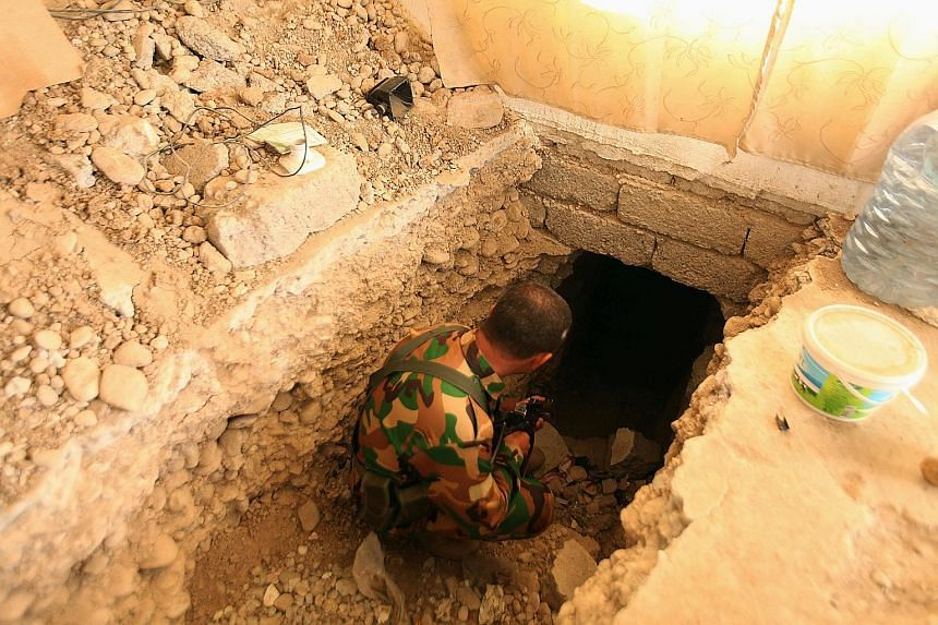 Right: One of the drills used by ISIS to bore through rock and construct tunnels. Below: A Peshmerga soldier inspecting a tunnel used by ISIS militants, on the outskirts of Bartila east of Mosul.