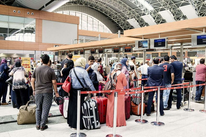 Passengers wait in line inside Sabiha Gokcen International Airport in Istanbul on July 17, 2016.