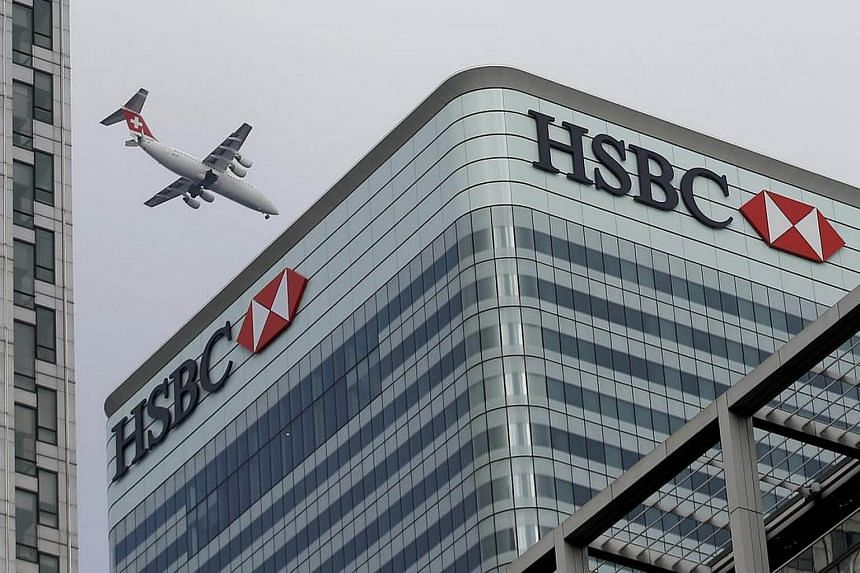 An aircraft flies past the HSBC headquarters building in the Canary Wharf financial district in east London.