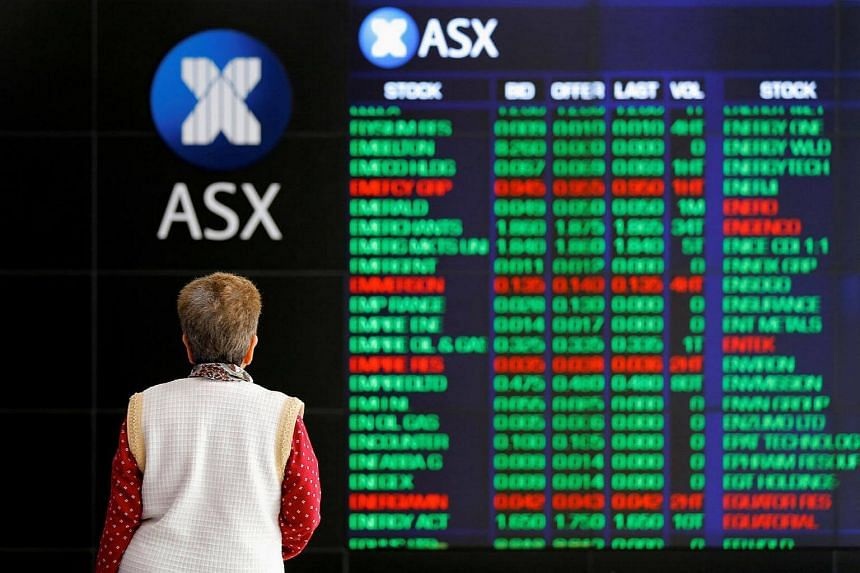 An investor looks at a board displaying stock prices at the Australian Securities Exchange in Sydney, Australia.