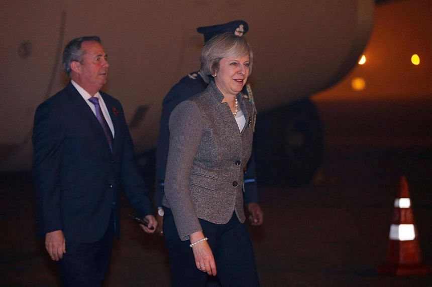 Britain's Prime Minister Theresa May walks towards her car after her arrival at the airport in New Delhi.