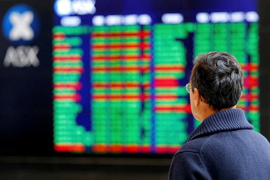 An investor looks at a board displaying stock prices at the Australian Securities Exchange (ASX) in Sydney, Australia.
